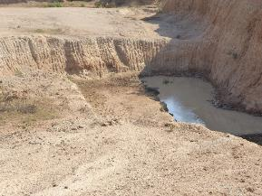 Borrow pit collecting and storing surface runoff (Chokwe, Mozambique)